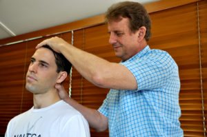 Townsville-Chiropractor-examining a patients neck movement